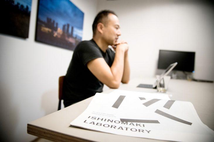 「タフなデザインは生き残る」と話す芦沢さん。テーブルの上にあるのは、石巻工房の広報誌