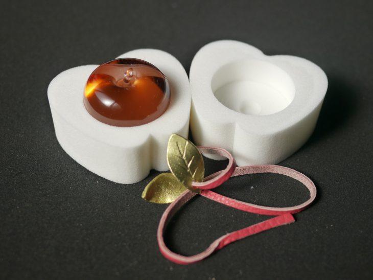 「スミファ」用に3社がコラボして製作したリンゴ。サトウ化成ではウレタン製ケースと革ひもを製造