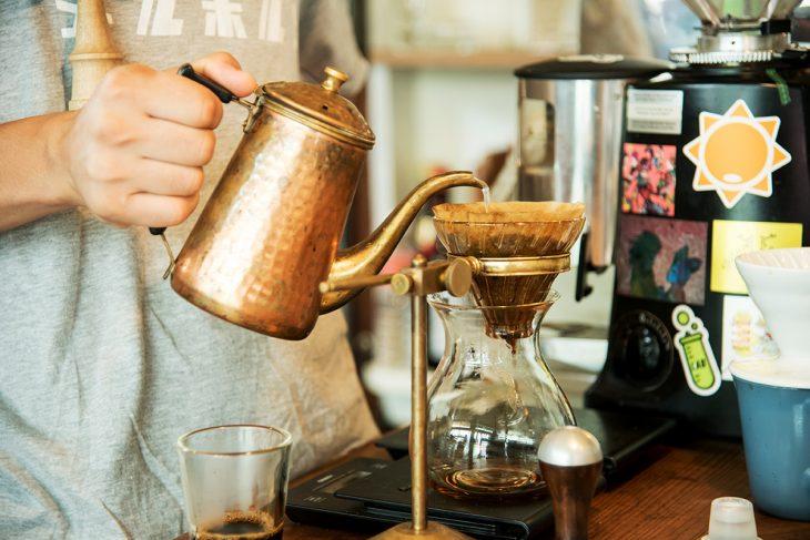 ハンドドリップでコーヒーを提供している。店内にはコーヒー豆の焙煎機も