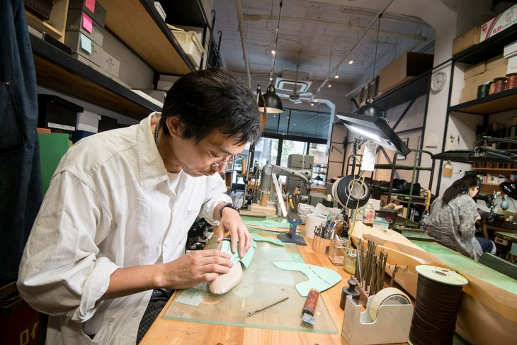 型紙を木型に合わせている吉見さんと、奥でミシンをかけているスタッフ