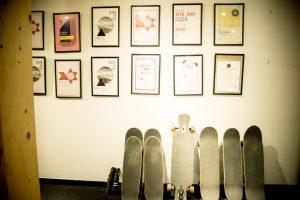 ウェブ制作で受賞した賞状の数々。その下にはスタッフが使っているスケートボードが置かれている