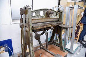 試作品を作るための古い道具が並ぶ。写真は紙にスジを入れるための機械。